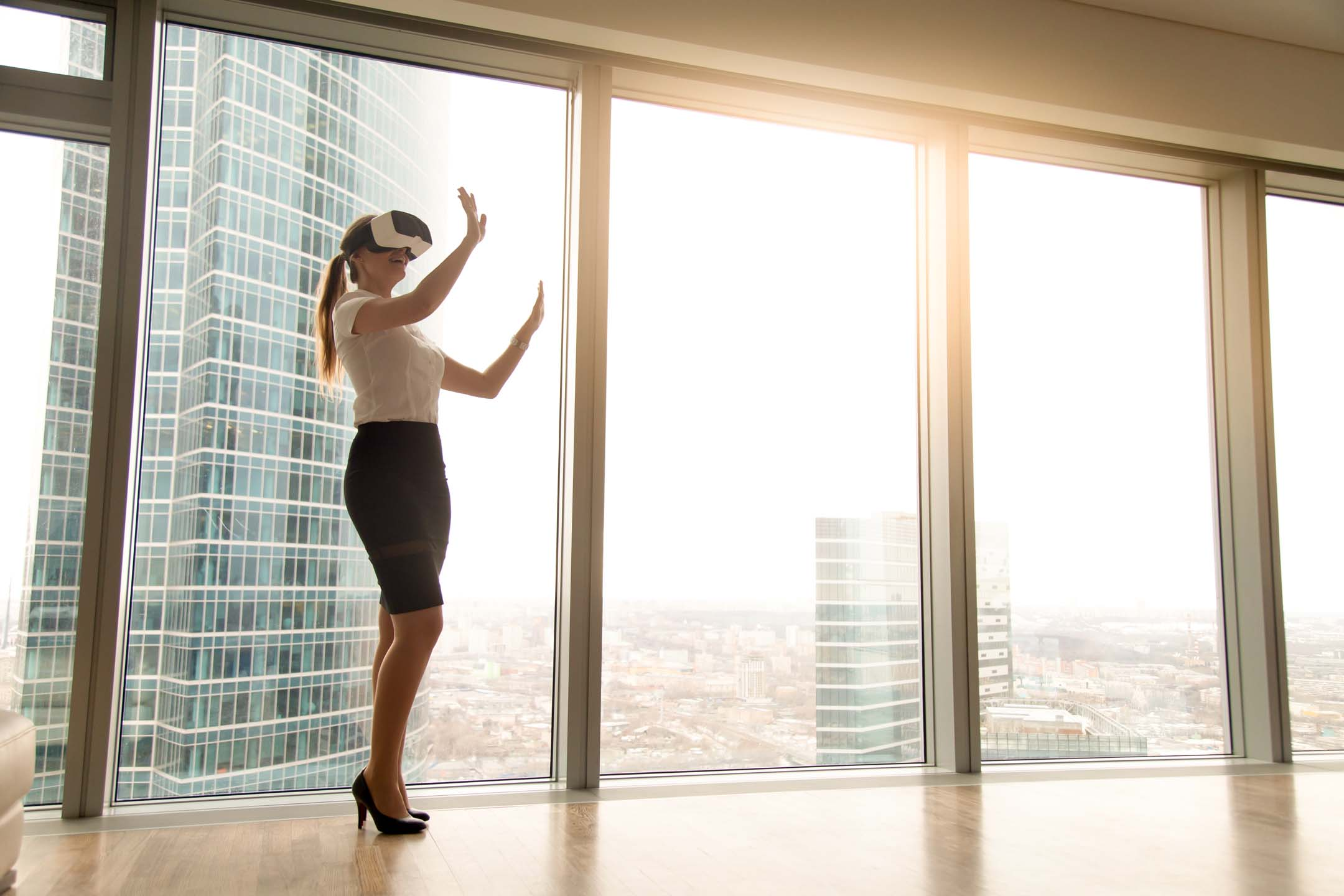 Excited businesswoman wearing headset exploring vr standing near